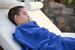 Little boy resting by the pool. Six year old boy wrapped in a towel resting after a swim in the oceanside pool on the Greek island of Crete Stock Images