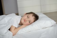 Little boy resting in white bed with eyes open Royalty Free Stock Image
