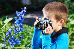 Little boy with retro camera shooting flowers Royalty Free Stock Images