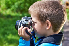 Little boy with retro camera shooting Royalty Free Stock Photos
