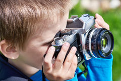 Little boy with retro camera shooting Stock Photos