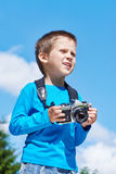 Little boy with retro camera on sky looks into distance Royalty Free Stock Photography