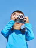 Little boy with retro SLR camera on blue sky Royalty Free Stock Photo