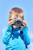 Little boy with retro SLR camera on blue sky Stock Photo