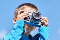 Little boy with retro SLR camera on blue sky Stock Photography