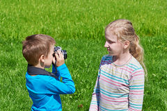 Little boy with retro SLR camera shooting girl Stock Image