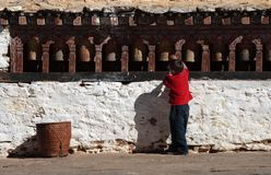 Little boy revolving the prayer wheels Stock Photos