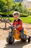 Little boy ridding his yellow toy motorcycle. On the park alley in a sunny day Royalty Free Stock Photos