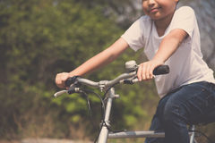 Little boy ride bicycle on the rock road. Vintage color, Selective focus at hand of Young boy wear blue jean ride an vintage color old bicycle on the stone royalty free stock photo