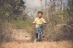 Little boy ride bicycle on the rock road. Royalty Free Stock Images