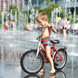 Little boy rides his bike among fountains Stock Photography