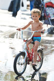 Little boy rides his bike among puddles Royalty Free Stock Photo