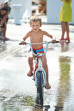 Little boy rides his bike among puddles Royalty Free Stock Photos