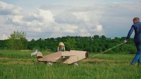A little boy rides a homemade cardboard plane. Concept of friendly family. A little boy rides a homemade cardboard plane. Father rolling a little boy dressed as stock video