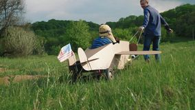 A little boy rides a homemade cardboard plane. Concept of friendly family. A little boy rides a homemade cardboard plane. Father rolling a little boy dressed as stock video footage