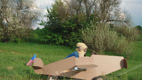 A little boy rides a homemade cardboard plane. Father rolling a little boy dressed as a pilot on a cardboard airplane on nature. Concept of friendly family stock video