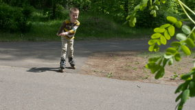 Little boy rides on roller skates in the park stock footage