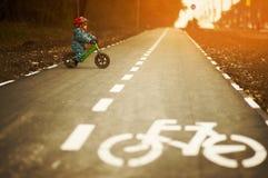Little boy riding a balance bike. On a cycling way Stock Photo
