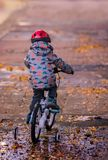 Little boy riding on a bicycle in the evening. Little boy wearing red protective helmet riding on a bicycle in the evening after rain royalty free stock image