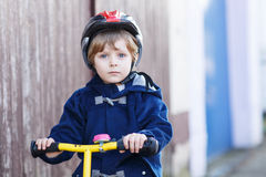 Little boy riding bicycle in village or city Royalty Free Stock Images