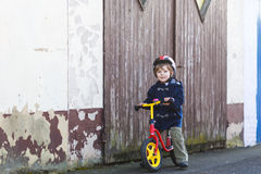 Little boy riding bicycle in village or city Stock Image