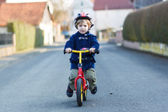 Little boy riding bicycle in village or city Stock Photo