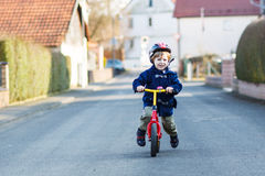 Little boy riding bicycle in village or city Royalty Free Stock Photos