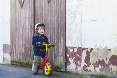 Little boy riding bicycle in village or city Stock Images