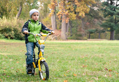 Little boy riding bike outdoors on Stock Photography