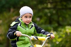 Little boy riding bike outdoors Stock Images