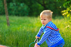 Little boy riding bike in the park Stock Photo