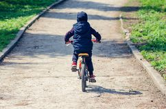 Little boy riding a bike in the spring city park.  stock images
