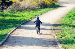 Little boy riding a bike in the spring city park.  royalty free stock image