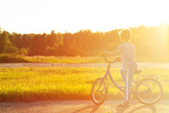 Little boy riding bike in summer park at sunset Stock Images