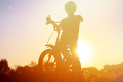 Little boy riding bike at sunset Stock Photo