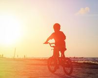 Little boy riding bike at sunset Royalty Free Stock Images