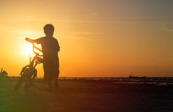 Little boy riding bike at sunset Stock Photos