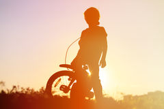 Little boy riding bike at sunset, kids sport stock photos
