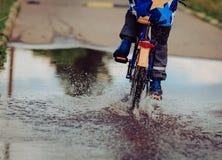 Little boy riding bike in water puddle. Kids seasonal activities Stock Photo