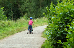 Little boy riding bike through woods Stock Photography