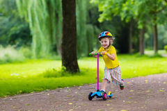 Little boy riding a colorful scooter Stock Photos