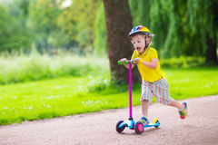 Little boy riding a colorful scooter. Little child learning to ride a scooter in a city park on sunny summer day. Cute preschooler boy in safety helmet riding a Stock Photos