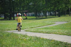 Little boy riding his bicycle on a twisting narrow road Royalty Free Stock Photography