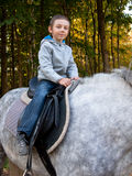 Little boy riding a horse. On a background of forest Royalty Free Stock Photography
