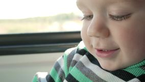 The little boy is riding in a moving train near the window. He smiles and looks at the book. Close-up.  stock video