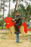Little boy riding an orange horse at the playground. Happy baby child riding an orange horse at the playground stock images