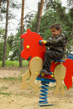 Little boy riding an orange horse at the playground. Happy baby child riding an orange horse at the playground Royalty Free Stock Image