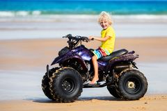 Child on quad bike at beach. All-terrain vehicle. Little boy riding quad bike on tropical beach. Cute blond curly child on quadricycle. All-terrain vehicle ride Royalty Free Stock Images