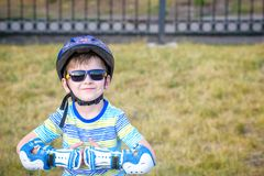 Little boy riding on rollers in the summer in the Park. Happy ch stock photography