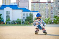 Little boy riding on rollers in the summer in the Park. Happy child in helmet learning to skate royalty free stock photo